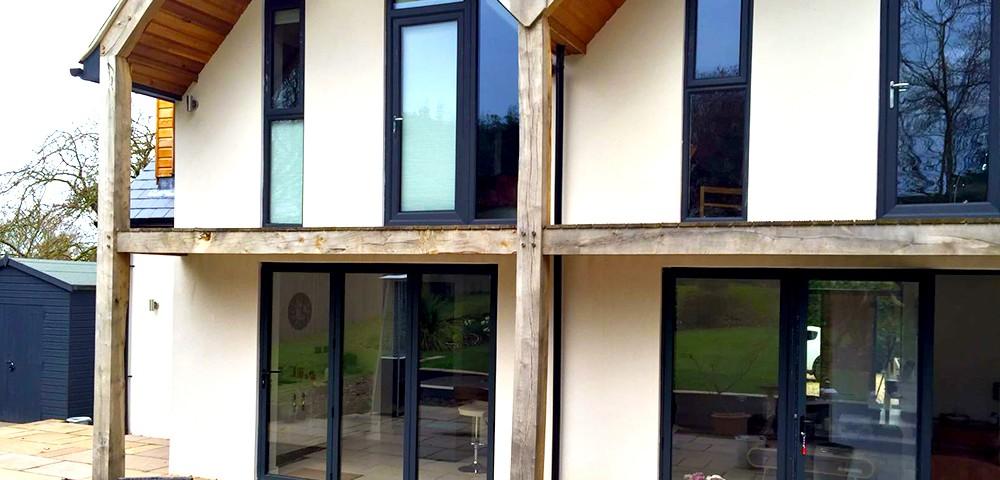 three sets of grey bi-fold doors with matching windows in nottingham