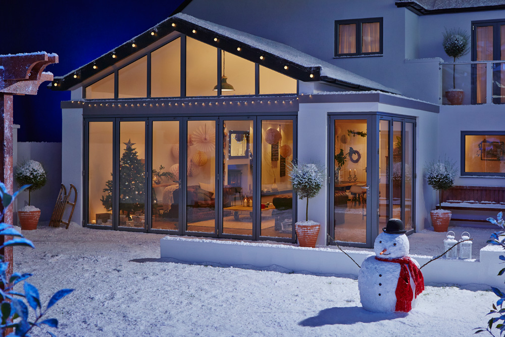 An origin bi-fold door in winter with a garden full of snow and a snow man