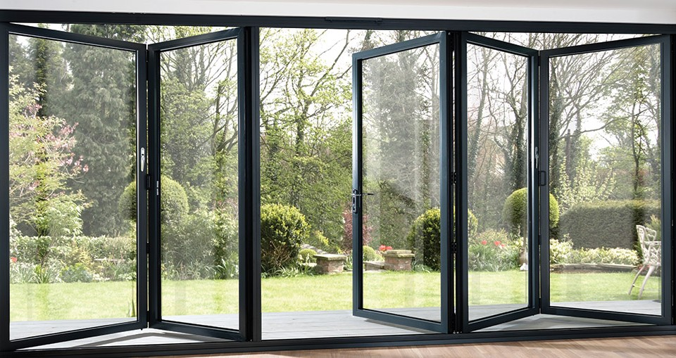Grey 5 pane bi-folding door opening out into a garden