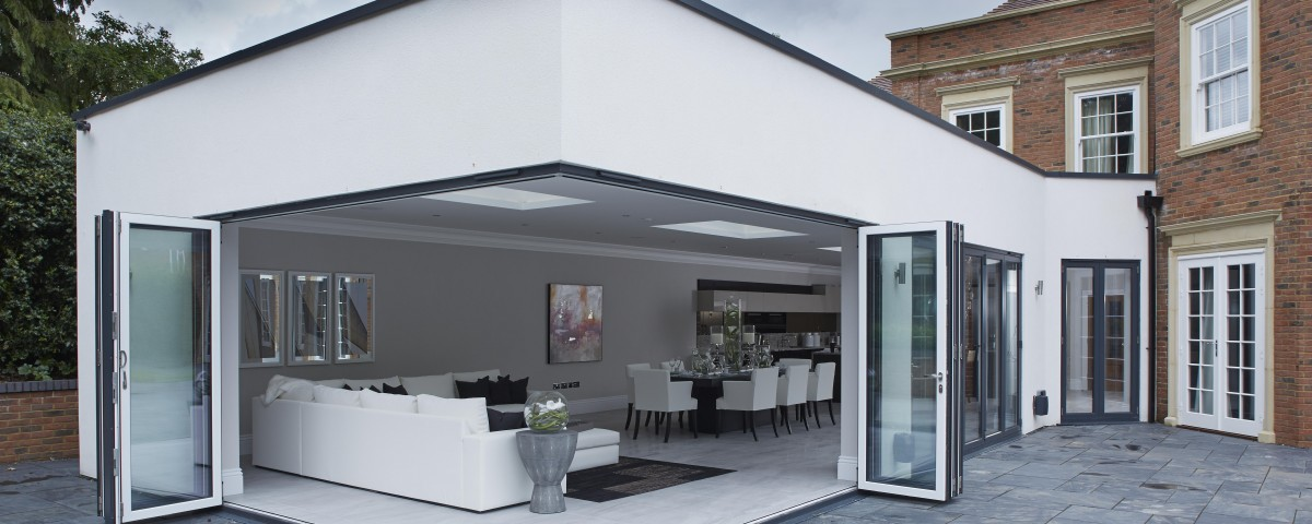Origin grey on white corner bi-fold door on a white rendered extention